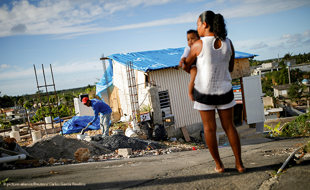amuel Vasquez rebuilds his house, which was partially destroyed by Hurricane Maria, while his wife Ysamar Figueroa looks on, whilst carrying their son