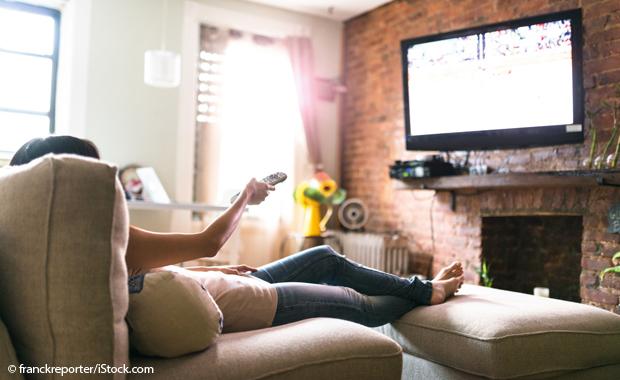 La personne est allongée sur le canapé et regarde la télévision.