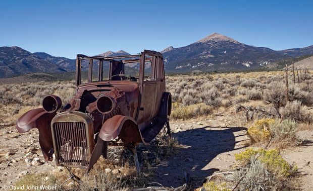 A rusted-out historical car with Wheeler Peak in the background at Great Basin National Park