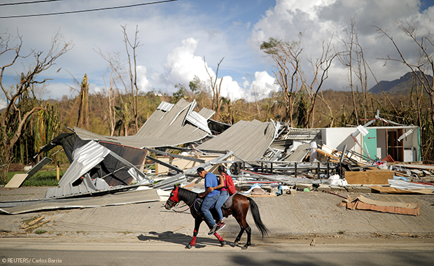 Locals ride a horse by a destroyed building in Jayuya, Puerto Rico, in October 2017, after Hurricane Maria