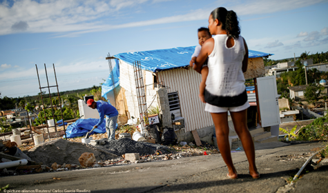 Samuel Vasquez rebuilds his house, which was partially destroyed by Hurricane Maria, while his wife Ysamar Figueroa looks on, whilst carrying their son
